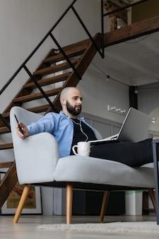 Facet w niebieskiej koszuli i czarnych dżinsach siedzi na kanapie i pracuje przy komputerze. pojęcie pracy na zlecenie
