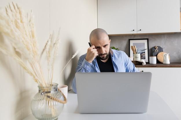 Facet w niebieskiej koszuli i czarnych dżinsach uczy się online w domu, siedząc przy biurku przy komputerze