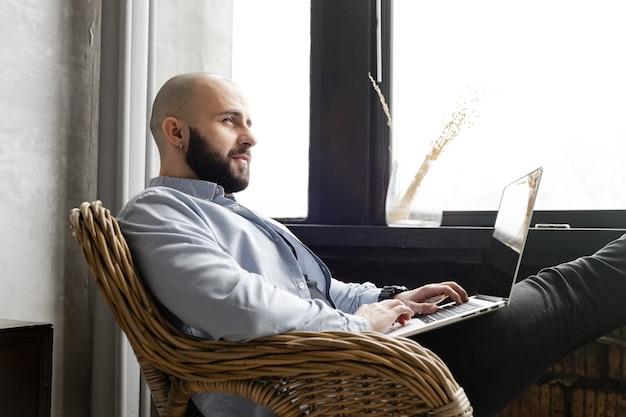 Facet w niebieskiej koszuli pracuje na laptopie w domu przy oknie. koncepcja pracy zdalnej