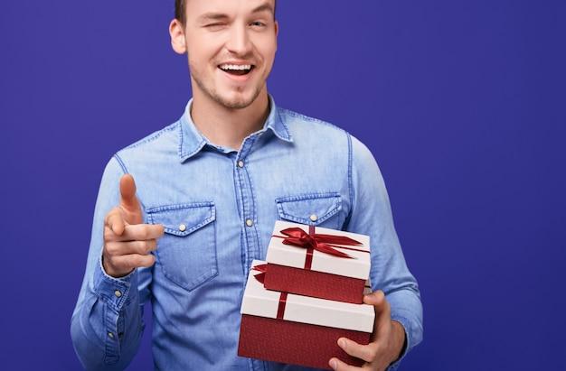 Facet w niebieskiej koszuli stojący z dwoma prezentami i wskazujący palcem wskazującym prosto