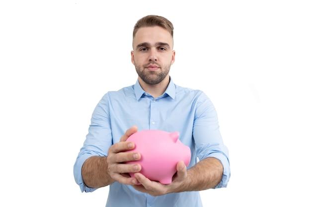 Facet w niebieskiej koszuli trzyma różową skarbonkę