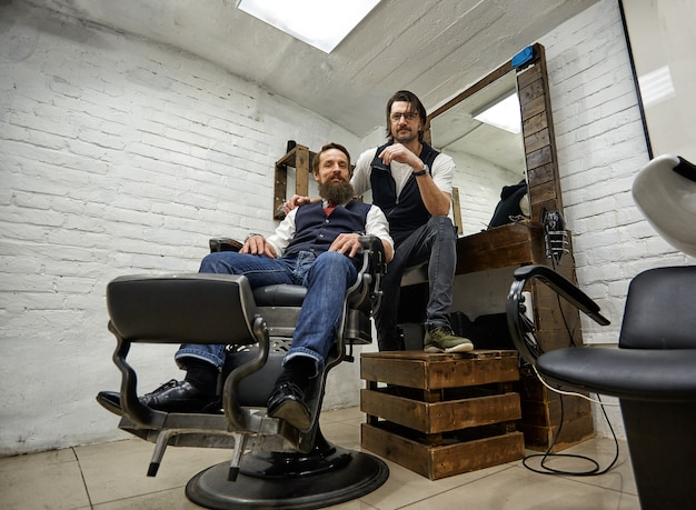 Facet w nowoczesnym sklepie fryzjerskim. fryzjer sprawia, że fryzura jest mężczyzną z długą brodą. mistrz fryzjer robi fryzurę nożyczkami i grzebieniem