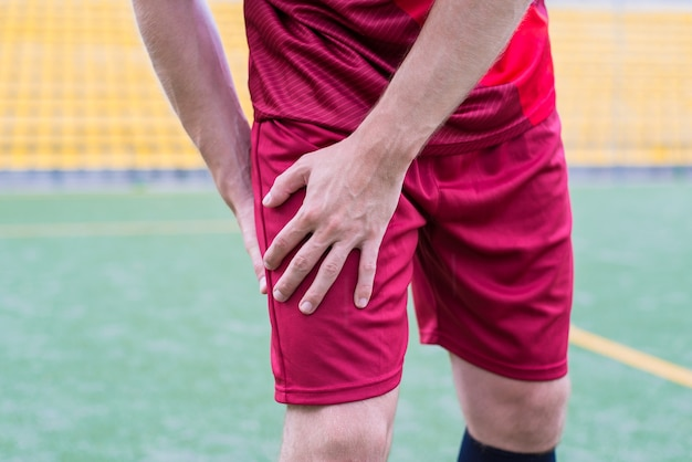 Facet w odzieży sportowej trzyma biodro