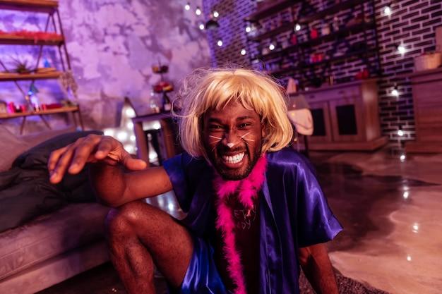 Facet w peruce. uśmiechnięty pozytywny facet ubrany w niebieską kobiecą szatę i perukę fryzurę bob jest pijany i szczęśliwy