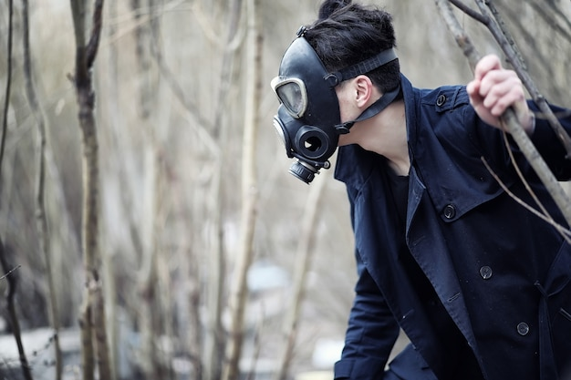 Facet w płaszczu i masce gazowej. postapokaliptyczny portret azjaty zamaskowany przed promieniowaniem. chłopiec jest koreańczykiem w masce od zatrucia gazami. maska postnuklearna na azjatów.