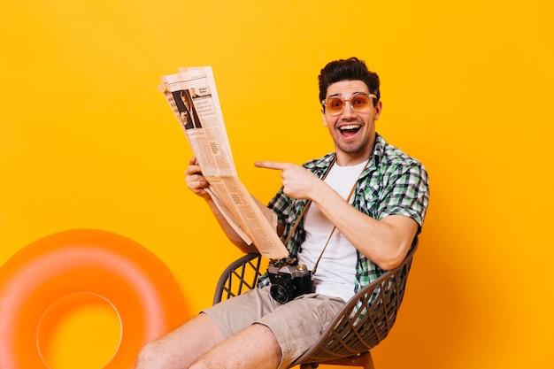 Facet w pomarańczowych okularach wskazuje na gazetę. mężczyzna z kamerą retro siedzi na krześle na pomarańczowej przestrzeni.