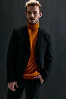 Facet w pomarańczowym swetrze i ciemnej kurtce na szarym tle przycięty widok modelu