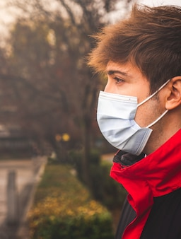 Facet w profilu z maską ochronną w parku w zimowy dzień