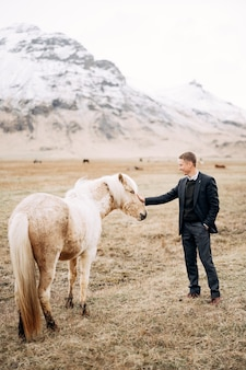 Facet w spodniach, swetrze i kurtce głaszcze kremowego konia po pysku i grzywie