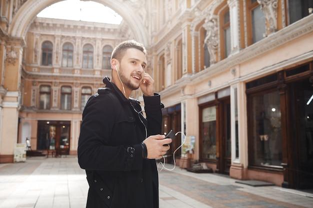Facet w starym centrum handlowym. spacerując, słuchając muzyki.