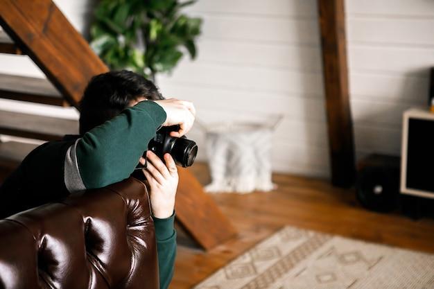 Facet w zielonym swetrze z aparatem w rękach zdejmuje wnętrze. poziome zdjęcie