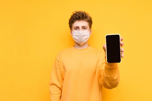 Facet w żółtej bluzie i masce ochronnej z gazy stoi na pomarańczowo i pokazuje aparatowi smartfon z czarnym ekranem. koronawirus pandemia. kwarantanna. covid19.