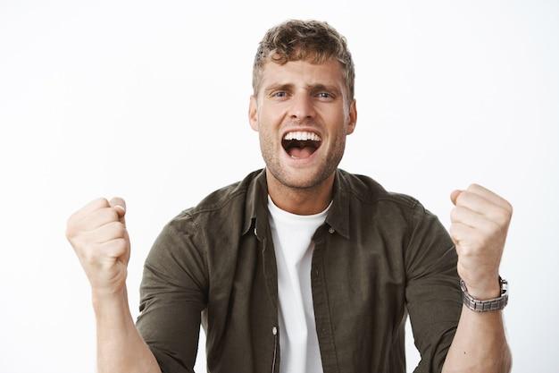 Facet wiwatujący z podekscytowania i radości krzyczy do przodu wspierające słowa, zaciskając pięści z radości i będąc asertywnym, wzmacniając pewność siebie, zachęcaj przyjaciela do działania, pozując nad szarą ścianą