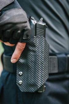 Facet wkłada broń do kabury z bliska