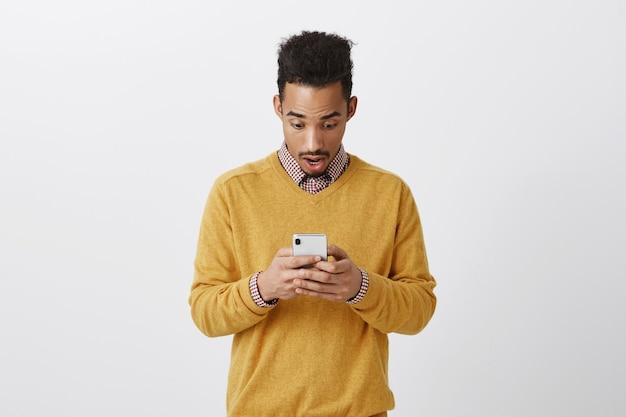Facet wpisał swoje objawy w internecie, czując się zszokowany. portret podekscytowanego, zdumionego ciemnoskórego mężczyzny z fryzurą afro, opadającą szczęką i sapaniem, gubiącego mowę podczas czytania wiadomości na smartfonie