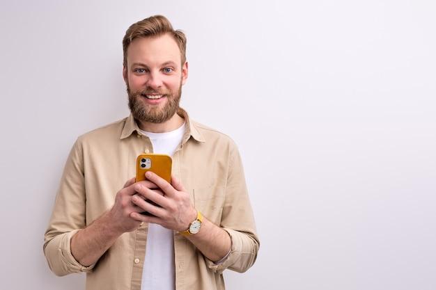 Facet wpisujący wiadomość do kogoś na smartfonie, mającego przyjemny uśmiech