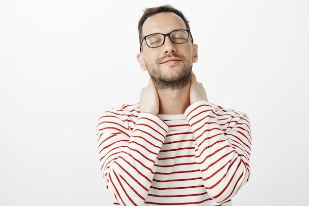 Facet wspomina miłe uczucie dłoni kochanków. zmysłowy romantyczny europejski wesoły model w okularach, zamykający oczy i unoszący głowę z lekkim delikatnym uśmiechem, dotykający szyi
