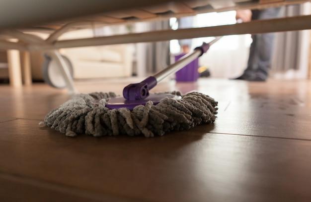 Facet wycierający kurz pod sofą w mieszkaniu