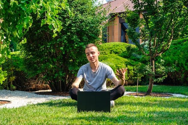 Facet z amputowaną ręką siedzi na trawniku i rozmawia z przyjaciółmi przez sieć społecznościową