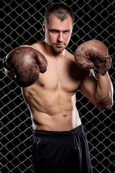 Facet z bokserskimi rękawiczkami pokazuje mięśnie na ogrodzeniu