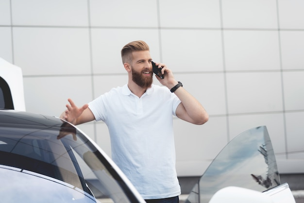 Facet z brodą rozmawia przez telefon w pobliżu swojego samochodu elektrycznego