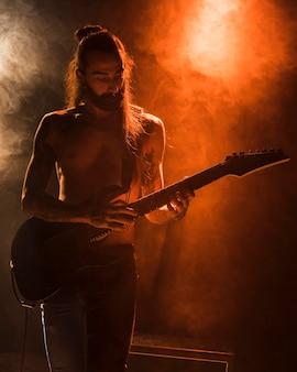 Facet z długimi włosami na gitarze stuka akordy