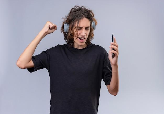 Facet z długimi włosami w czarnej koszulce słucha muzyki przez słuchawki na białej ścianie