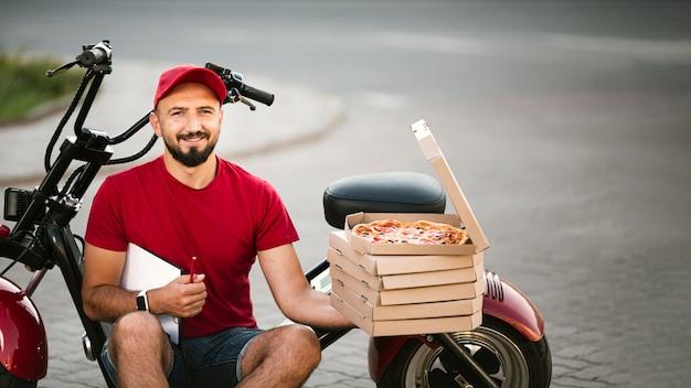 Facet z dostawą średnich strzałów siedzi na motocyklu