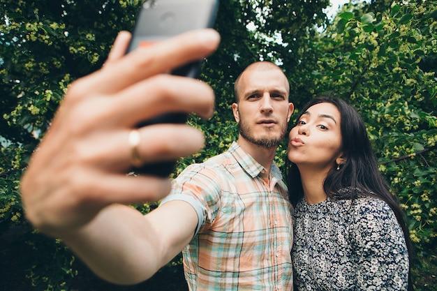 Facet z dziewczyną bierze selfies na zielonym ulistnieniu.