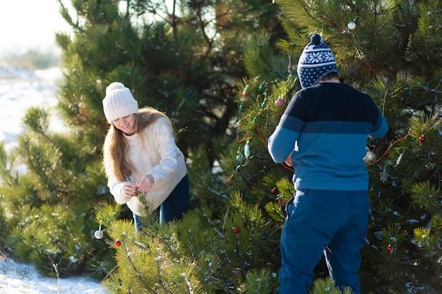 Facet z dziewczyną ozdabia zieloną choinkę na ulicy w zimie w lesie ozdobnymi zabawkami i girlandami. ozdoby na choinkę