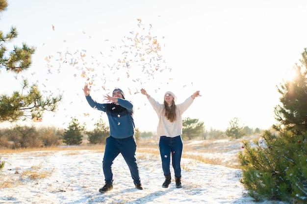 Facet z dziewczyną rzuca konfetti w zimowym lesie