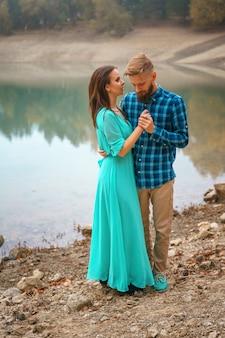 Facet z dziewczyną stojącą nad jeziorem w uścisku. romantyczny związek
