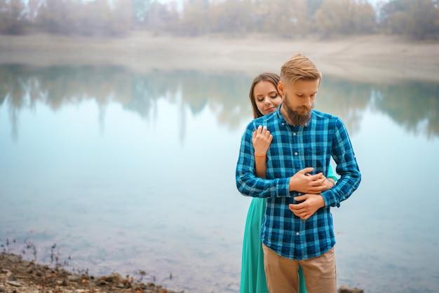Facet z dziewczyną stojącą nad jeziorem w uścisku.
