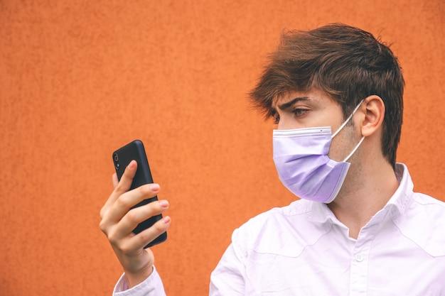 Facet z fioletową maską patrząc na swojego smartfona na pomarańczowym tle