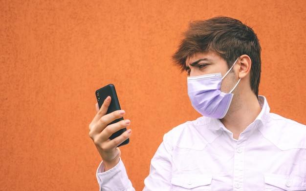 Facet z fioletową maską patrząc na swojego smartfona