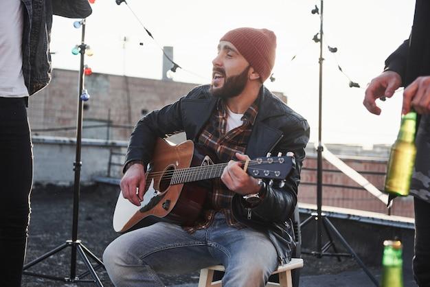 Facet z gitarą akustyczną śpiewa. przyjaciele bawią się na imprezie na dachu z dekoracyjnymi kolorowymi żarówkami