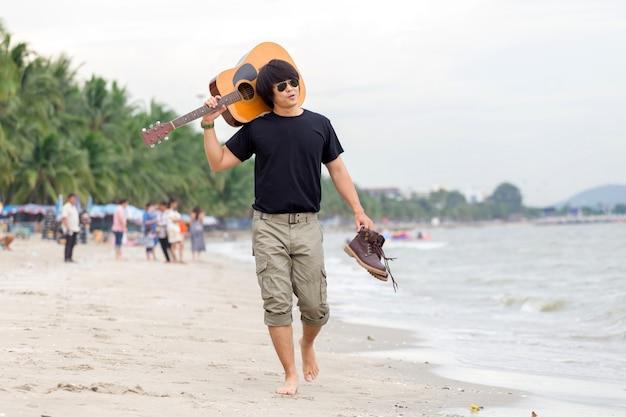 Facet z gitary pozycją na plaży, ładunków spodnia