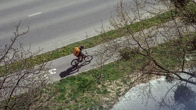 Facet z jedzeniem na rowerze z dużą pomarańczową torbą termiczną