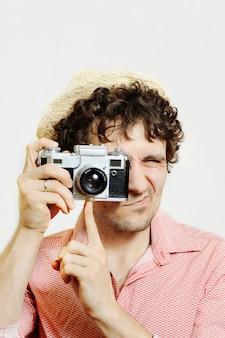 Facet z kędzierzawym włosy z kamerą na białym tle