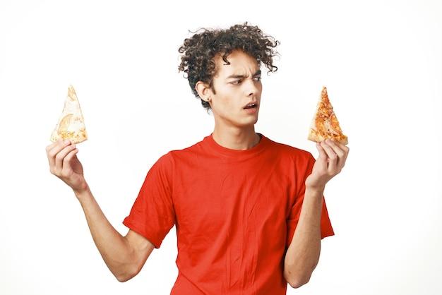 Facet z kręconymi włosami fast food w rękach jasne tło diety przekąski żywności