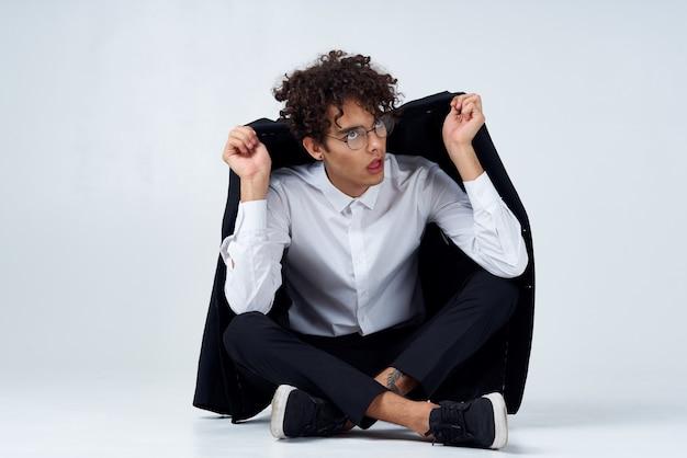 Facet z kręconymi włosami prostuje kurtkę na ramionach i siada na podłodze w trampkach i garniturze