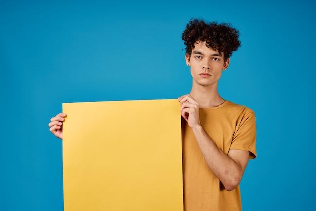 Facet z kręconymi włosami w rękach żółte plakaty