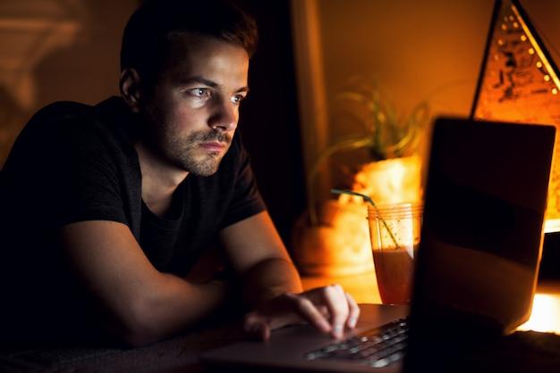 Facet z laptopem. oglądanie filmów i relaks w domu