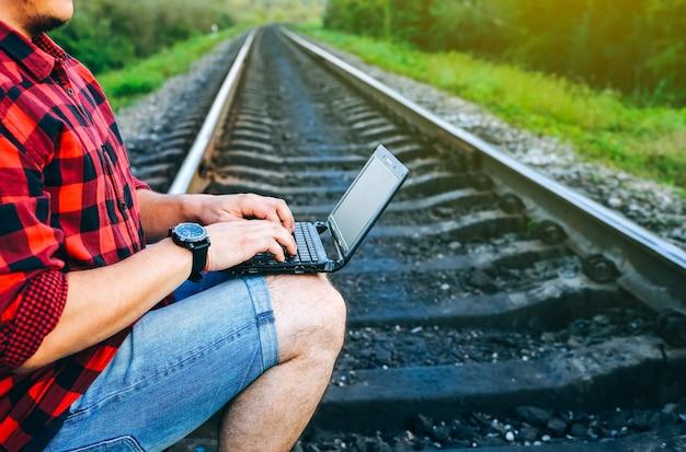 Facet z laptopem siedzi na torach kolejowych. niezależny pracownik hipster. człowiek pracuje podróżując.