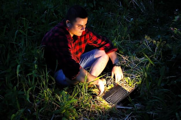 Facet z laptopem siedzi na trawie. niezależny pracownik hipster w nocy. człowiek pracuje podróżując.