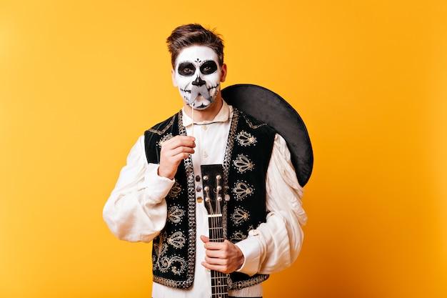 Facet z makijażem na halloween i sombrero za plecami bawi się i pozuje z fałszywymi wąsami.