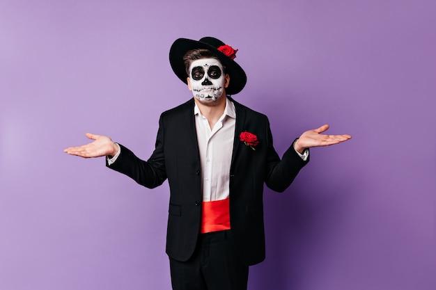 Facet z maską czaszki rozkłada ręce, nie będąc w stanie w żaden sposób pomóc. portret mężczyzny z niedowierzaniem, pozowanie na na białym tle.