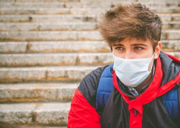 Facet z maską i plecakiem, patrząc na bok na schodach ulicznych w zimowy dzień