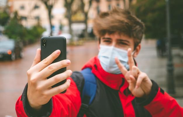 Facet z maską i plecakiem robiący selfie na ulicy w zimowy dzień