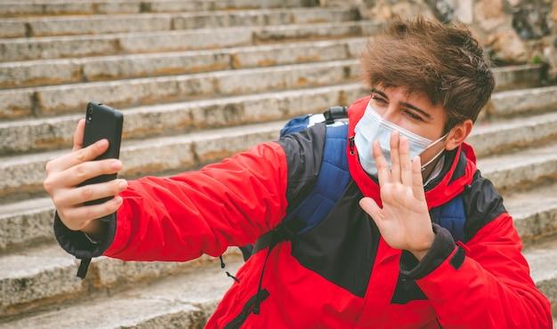 Facet z maską i plecakiem robiący selfie na ulicznych schodach w zimowy dzień